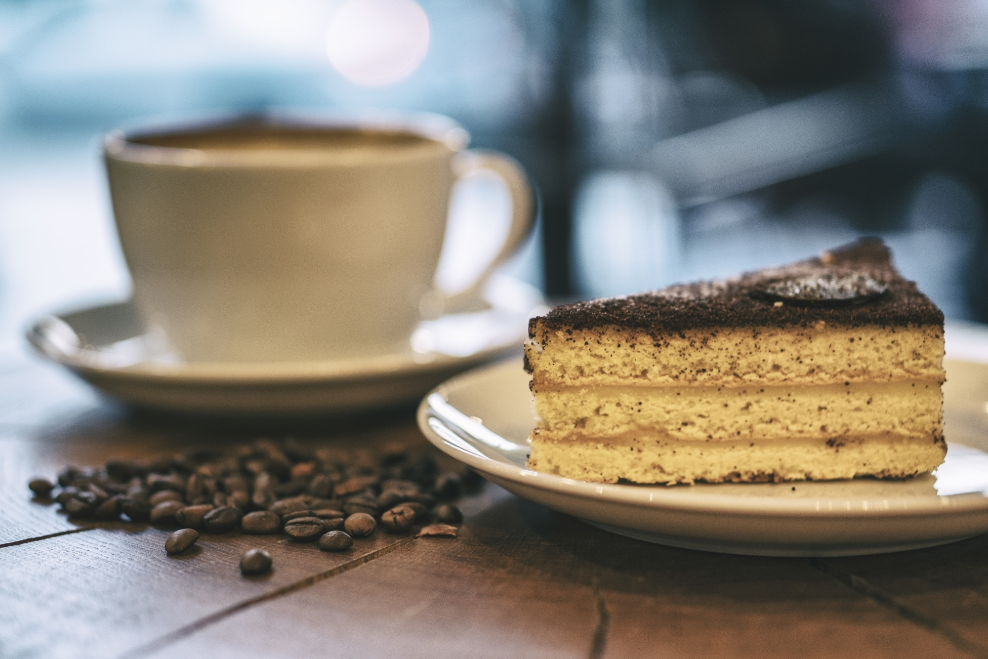 One cup of espresso and piece of cake on a wooden board